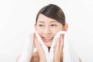 蒸しタオルを顔に当てている女性